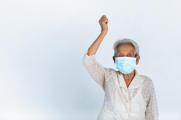 La abuela está levantando su mano en el aire sobre fondo blanco - campaña de máscara conceptual