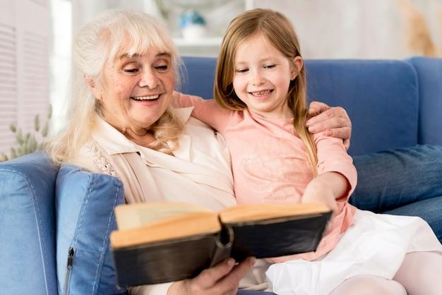 Abuela leyendo para niña en casa