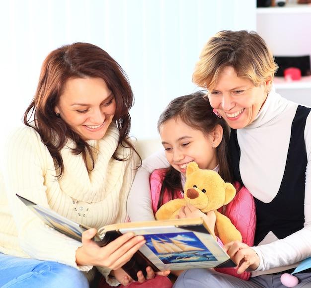 Abuela, madre e hija leyendo un libro juntas