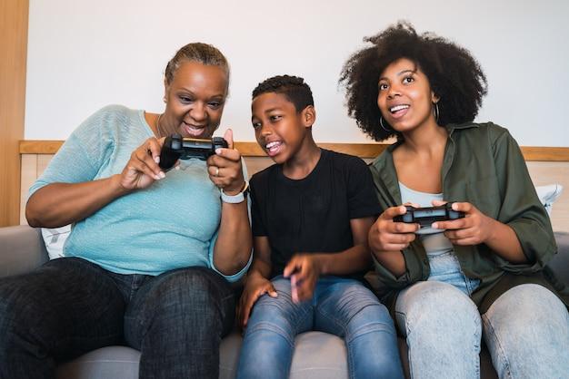 Abuela, madre e hijo jugando videojuegos en casa.