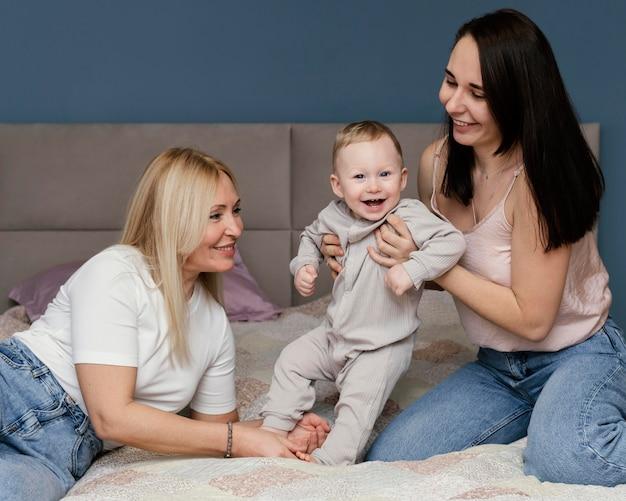Abuela y madre jugando en la cama con nieto