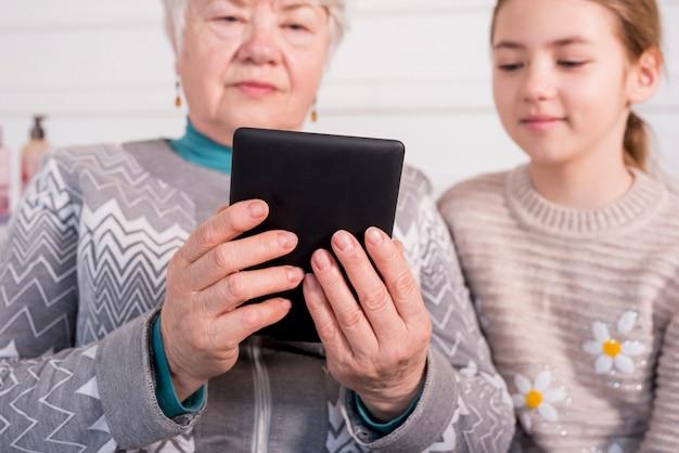 Abuela madura leyendo con su nieta
