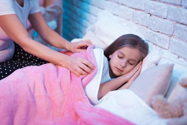 Abuela metiendo a la nieta para dormir por la noche en casa