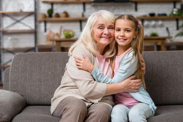 Abuela y nieta abrazando vista frontal