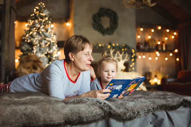 Abuela y nieta se divierten juntos leyendo un libro sobre la cama.