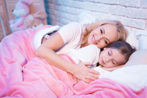 Abuela y nieta están acostadas en la cama.
