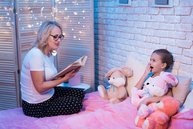 Abuela y nieta están leyendo un libro para niños por la noche en casa