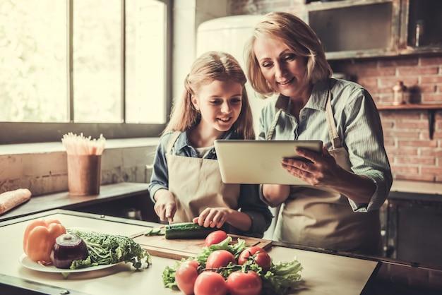 La abuela y la nieta están usando una tableta digital.