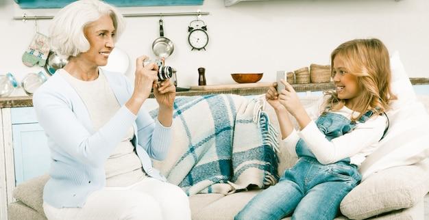 Abuela y nieta haciendo fotos de cada una usando diferentes tecnologías