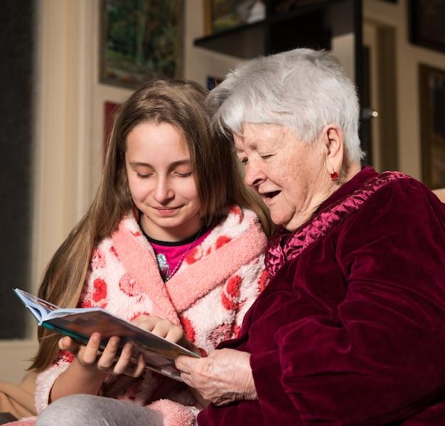 Abuela y nieta leyendo un libro en casa