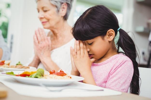 Abuela y nieta rezando en la mesa del comedor