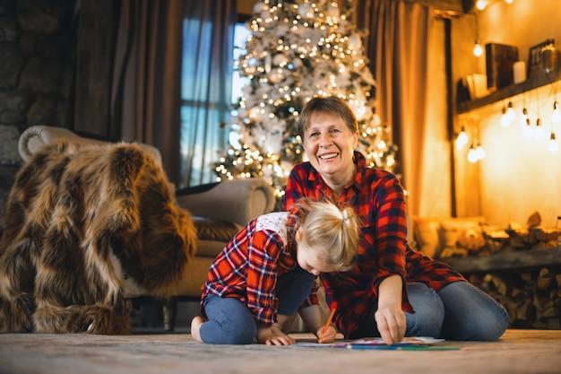Abuela y nieta sentadas en la alfombra frente al árbol y dibujan.