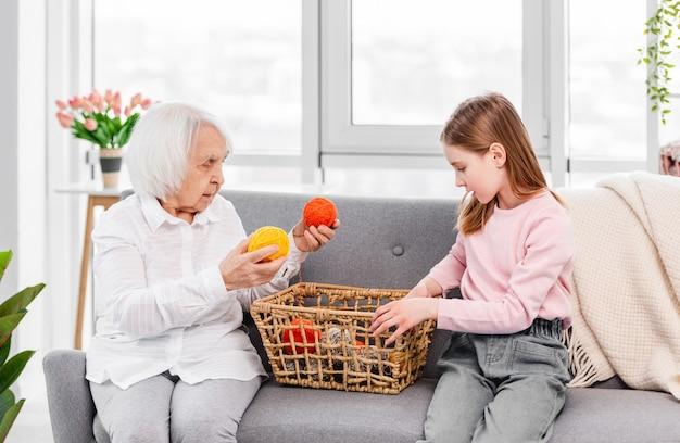 Abuela y nieta sentadas en el sofá en casa y mirando la canasta con bolas de hilo