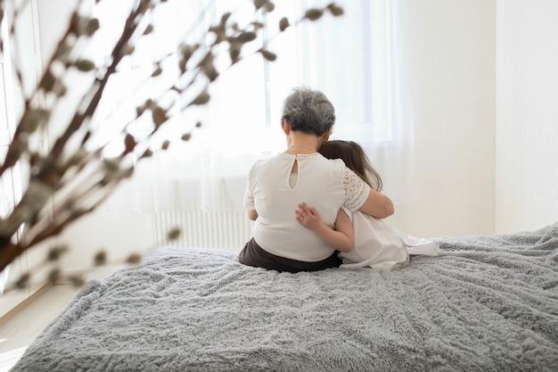 Abuela y nieta se sientan y abrazan.