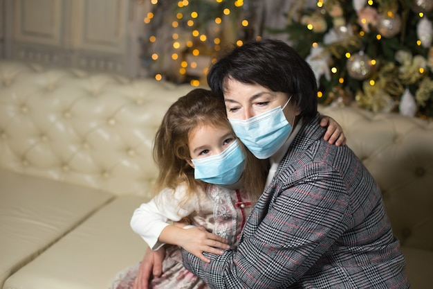 Abuela y nieta en el sofá de la sala de estar con decoración navideña abrazándose con máscaras médicas en la cara. unas vacaciones familiares durante el brote de coronavirus y enfermedad. año nuevo