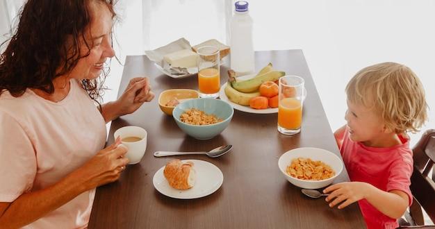 Abuela y nieto desayunan por la mañana en casa.