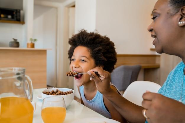 Abuela y nieto desayunando juntos.