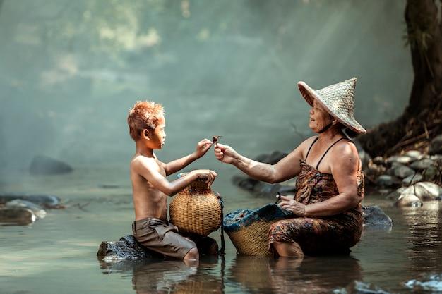 La abuela y el nieto tienen cangrejos para comer. después de que la abuela termina de cultivar arroz