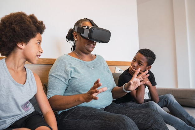 Abuela y nietos jugando con gafas de realidad virtual.