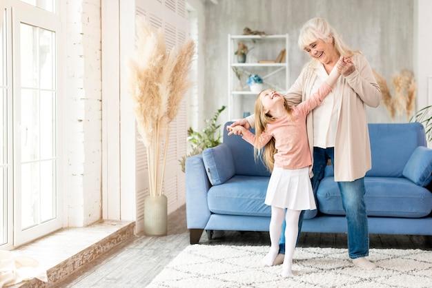 Abuela con niña en casa divirtiéndose