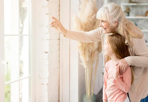 Abuela con niña en casa mirando por la ventana