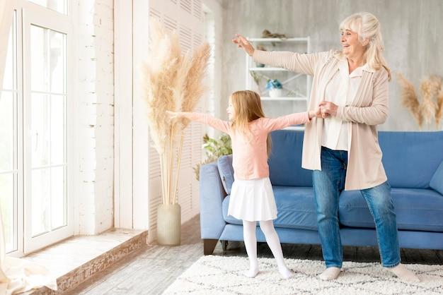 Abuela con niña en casa pasando tiempo juntos