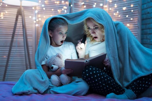Abuela con niña están leyendo libro debajo de la manta en casa