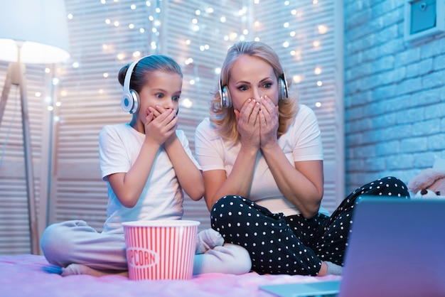 La abuela con la niña se estremece viendo la película en la noche