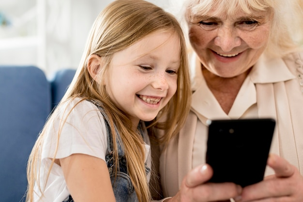 Abuela y niña mirando móvil