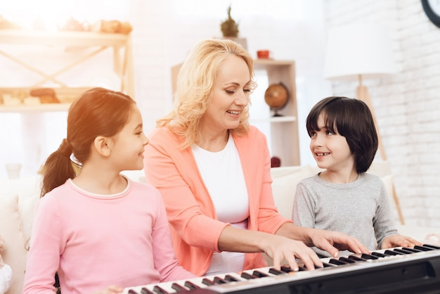 Abuela con niños enseñando a tocar el piano en casa