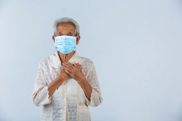 La abuela pone las manos en la cerradura y espera lo mejor.- campaña de máscara de cencept