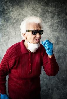 La abuela se protege de la infección por coronavirus con guantes médicos y mascarilla