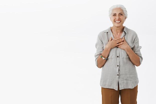 Abuela sonriente mirando agradecida, tocando el pecho complacido