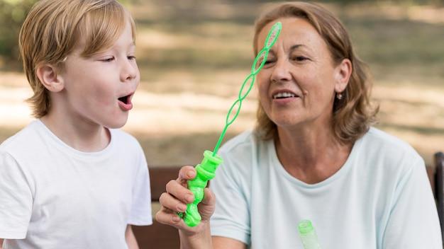 Abuela sonriente y niño haciendo globos