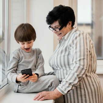 Abuela sonriente viendo a su nieto jugando con smartphone