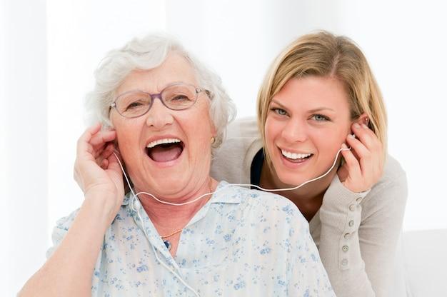 Abuela súper feliz y emocionada escuchando música con su nieta en casa