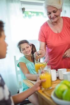 Abuela vertiendo jugo de naranja en vaso