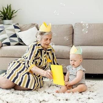 Abuela en vestido elegante jugando con nieto