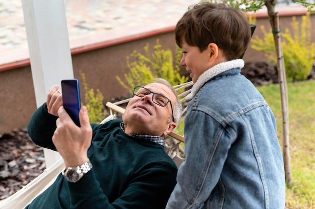 Abuelo afuera con su nieto sosteniendo un teléfono
