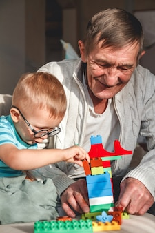 Abuelo anciano juega con su nieto con bloques de plástico
