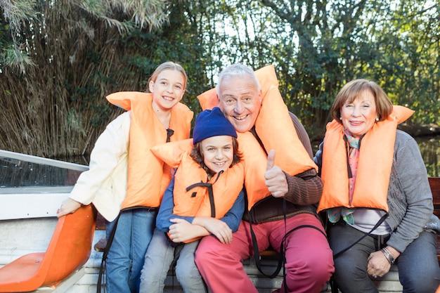 Abuelo feliz con su familia y mostrando el pulgar hacia arriba