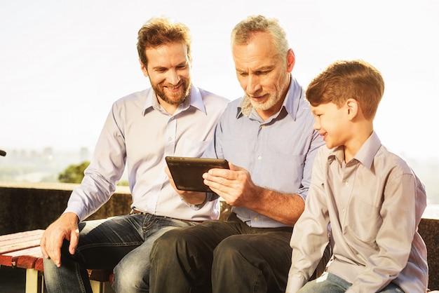 Abuelo con hijo y nieto siéntese en el banco.