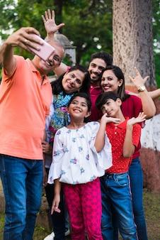 Abuelo indio tomando selfie - familia asiática de seis miembros de varias generaciones, capturando fotografías familiares en el teléfono inteligente mientras está de pie en el jardín o parque