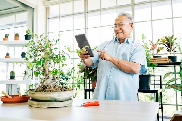 Abuelo de jubilación asiático usando una tableta digital para vender sus plantas de buena calidad en línea