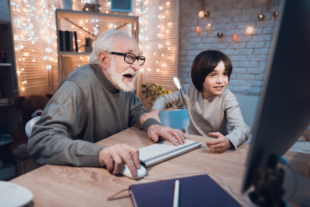 Abuelo jugando juegos de computadora con su nieto