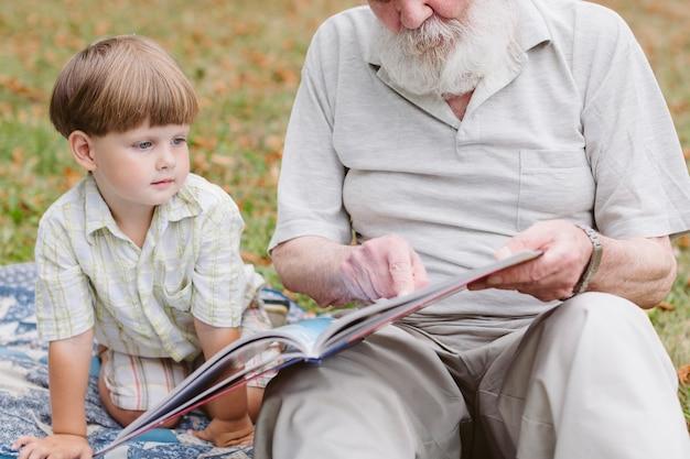 Abuelo leyendo para nieto al aire libre