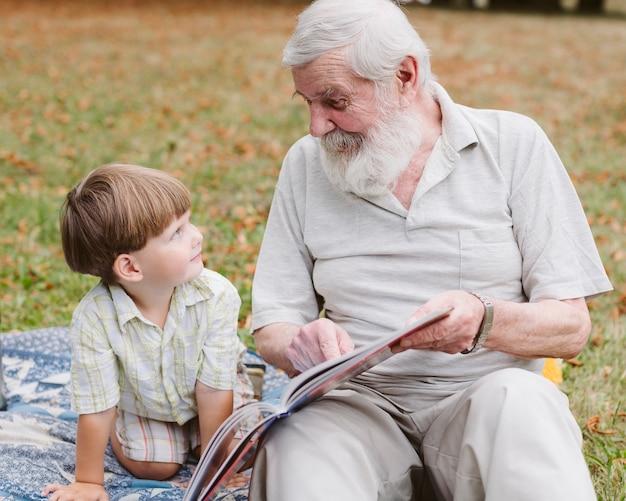 Abuelo leyendo para nieto en el parque