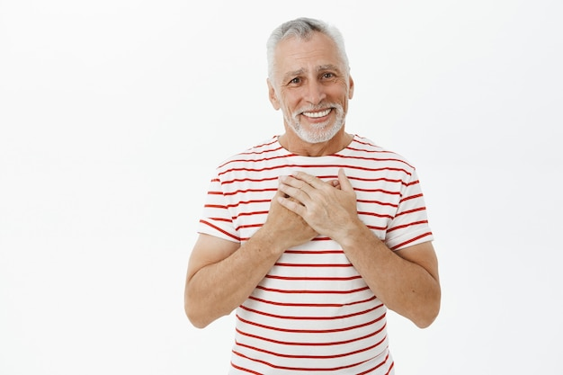 Abuelo mayor conmovido y halagado con barba que parece feliz y agradecido