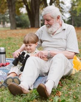 Abuelo mostrando binoculares a nieto