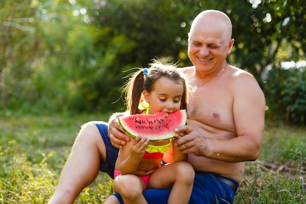 Abuelo y nieta comen una sandía en un jardín.